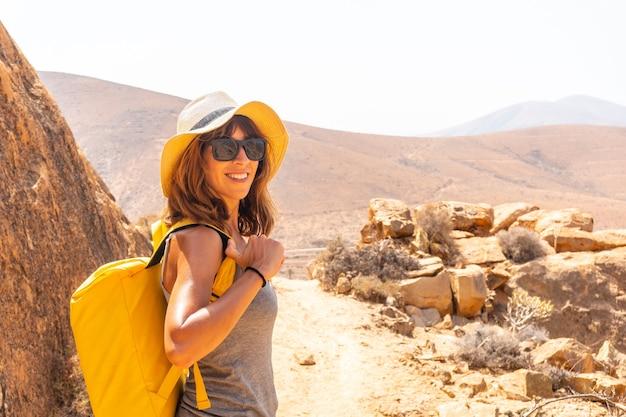 Retrato de uma menina alpinista com uma mochila amarela na trilha mirador de la peñitas no cânion peñitas, fuerteventura, ilhas canárias. espanha
