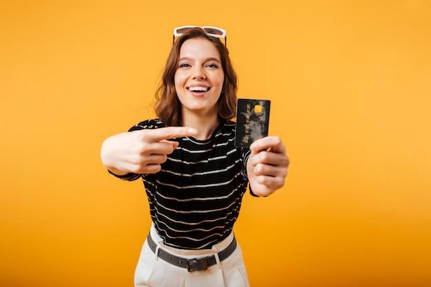 Retrato de uma menina animada, apontando o dedo no cartão de crédito