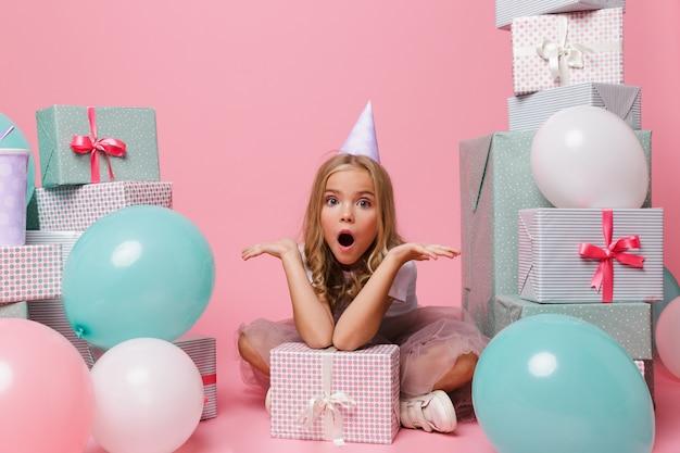 Retrato de uma menina animada em um chapéu de aniversário