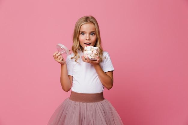Retrato de uma menina animada, segurando o frasco de marshmallow
