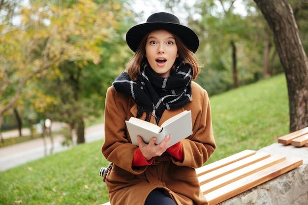 Retrato de uma menina animada, vestida com roupas de outono lendo