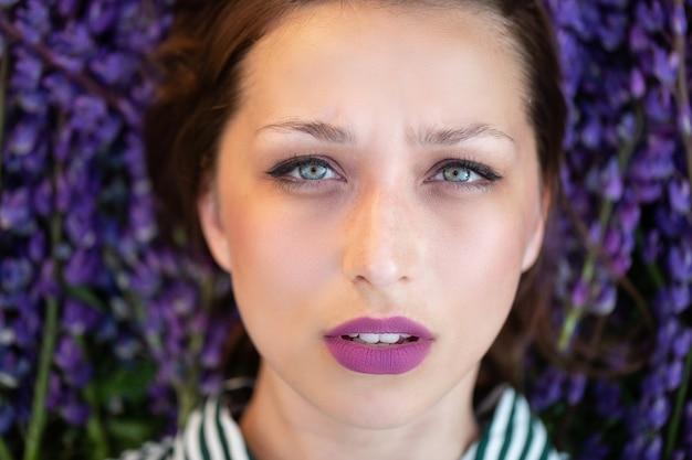 Retrato de uma menina ansiosa com lábios lilás deitada sobre flores roxas