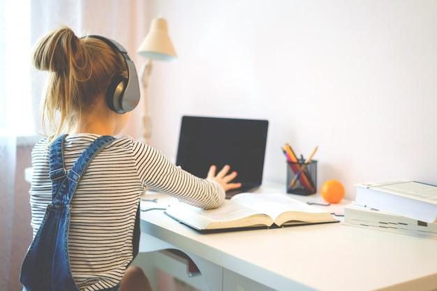 Retrato de uma menina aprendendo on-line com fones de ouvido e laptop, anotando em um caderno, sentado em sua mesa em casa fazendo lição de casa