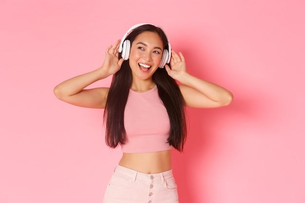 Retrato de uma menina asiática bonita e elegante curtindo música em fones de ouvido, parecendo sonhadora e otimista com um sorriso satisfeito, usando fones de ouvido sem fio, parede rosa de pé