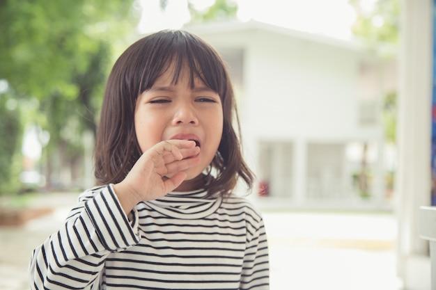 Retrato de uma menina asiática chorando com pequenas lágrimas rolando e chorando de emoção