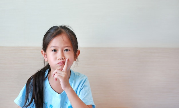 Retrato de uma menina asiática com rosto entediado de expressão, criança com o dedo na bochecha.