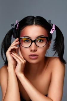 Retrato de uma menina asiática de óculos, um lindo rosto feminino com pele limpa e saudável, cabelo escuro com tranças, close-up sobre um fundo cinza.