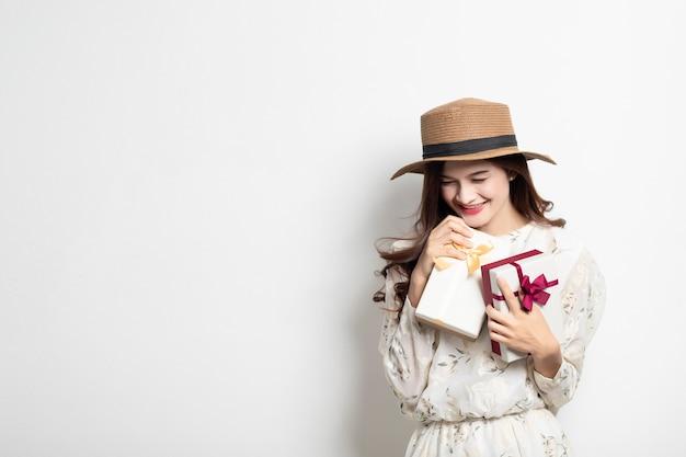 Retrato de uma menina asiática de sorriso feliz no vestido que guarda a caixa atual, menina tailandesa bonita com caixa de presente.