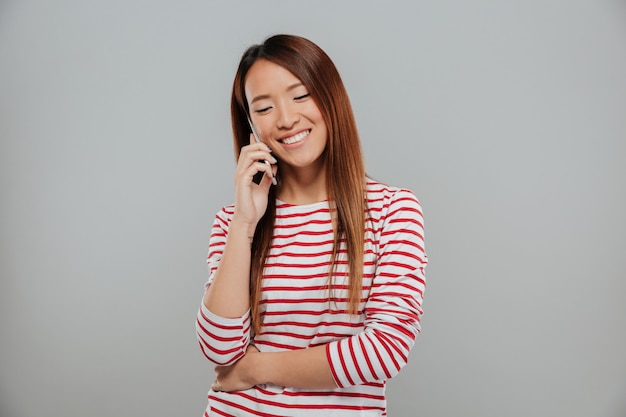 Retrato de uma menina asiática feliz falando no celular