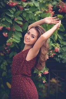 Retrato de uma menina asiática posando ao ar livre contra o arbusto de flores
