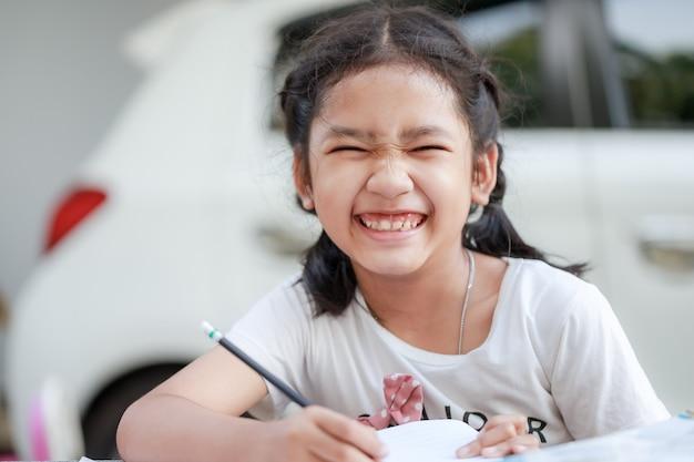Retrato de uma menina asiática sorrindo de felicidade, para aprender com o distanciamento social de casa e o conceito de quarentena, selecione o foco profundidade de campo rasa