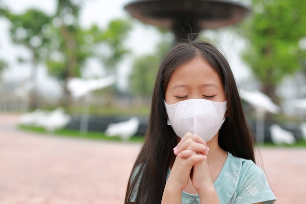 Retrato de uma menina asiática usando máscara facial e gesto de oração para parar covid-19 durante surto de coronavírus