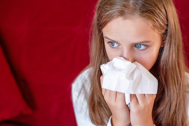 Retrato de uma menina assoando o nariz em um lenço na cabeça