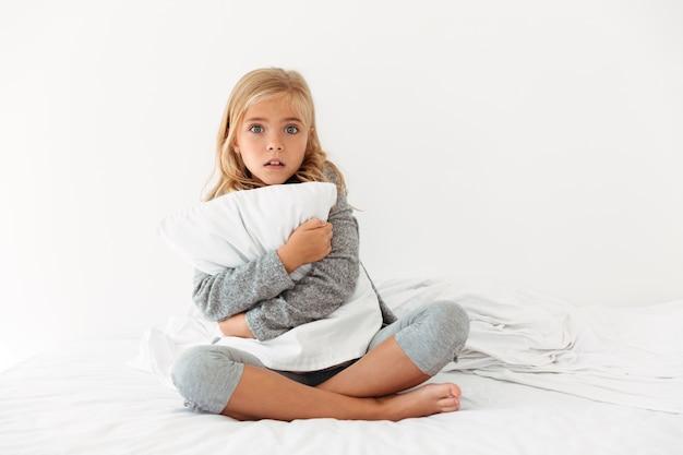 Retrato de uma menina assustada, abraçando o travesseiro