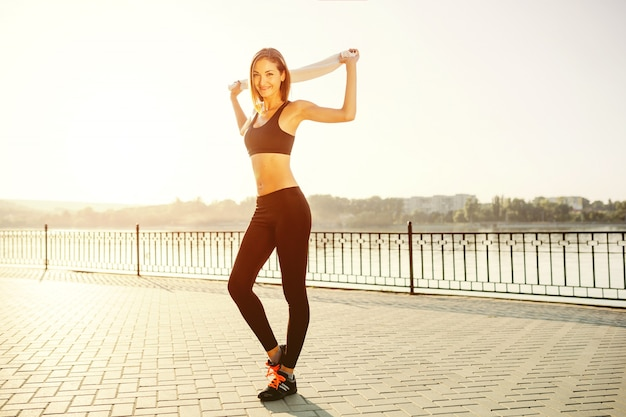 Retrato de uma menina atlética. modelo de fitness esporte jovem bonita se preparando para fazer jogging no parque da cidade.