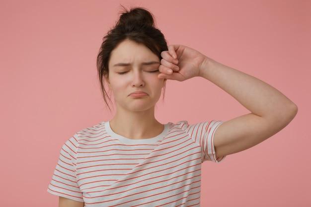 Retrato de uma menina atraente, chateada com cabelo castanho e coque. vestir t-shirt com tiras vermelhas e esfregar um olho. conceito emocional. fique isolado sobre uma parede rosa pastel