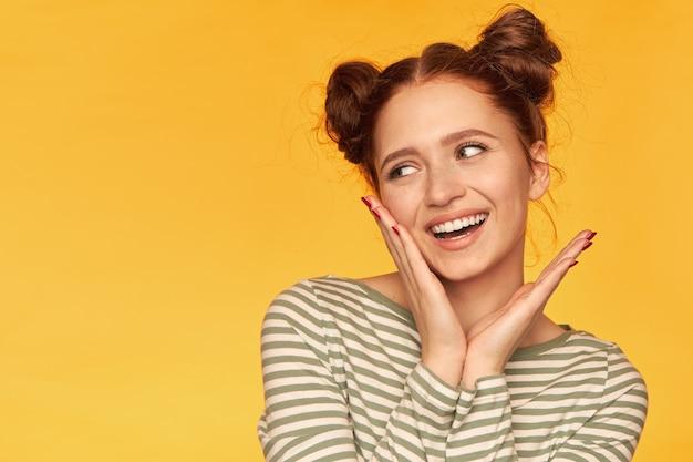 Retrato de uma menina atraente de cabelo vermelho com dois pãezinhos e pele saudável. vestindo um suéter listrado e tocando sua bochecha enquanto olha para a esquerda no espaço de cópia sobre a parede amarela
