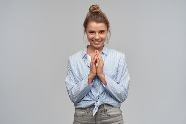 Retrato de uma menina atraente e adulta com cabelo loiro, reunido em um coque. vestindo camisa listrada com nó. mantenha as palmas das mãos juntas, tenha um plano. olhando para a câmera, isolada sobre uma parede cinza