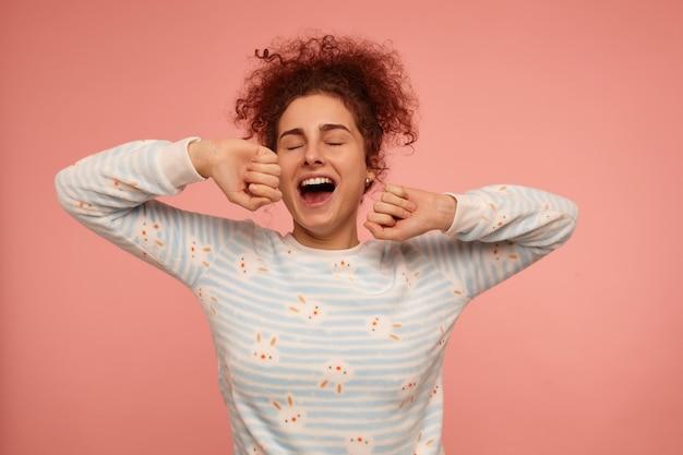 Retrato de uma menina atraente e adulta com cabelo ruivo cacheado. vestindo suéter listrado com coelhos e bocejos com os olhos fechados, alongamento. está com sono. fique isolado sobre uma parede rosa pastel