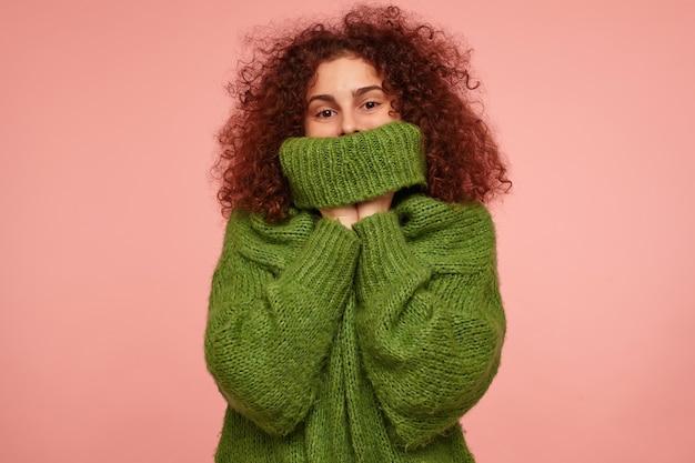 Retrato de uma menina atraente e adulta com cabelo ruivo cacheado. vestindo um suéter verde de gola alta e puxando um suéter sobre o rosto. isolado sobre parede rosa pastel