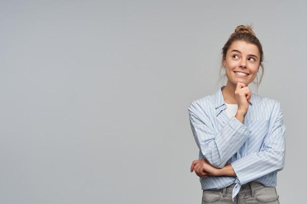 Retrato de uma menina atraente e adulta com coque de cabelo loiro.