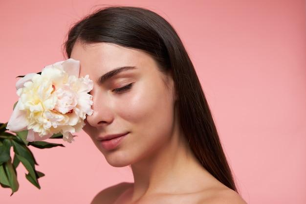 Retrato de uma menina atraente e bonita com longos cabelos castanhos e pele saudável, tocando o olho com uma flor, sonhando com os olhos fechados. suporte isolado, close-up sobre parede rosa pastel