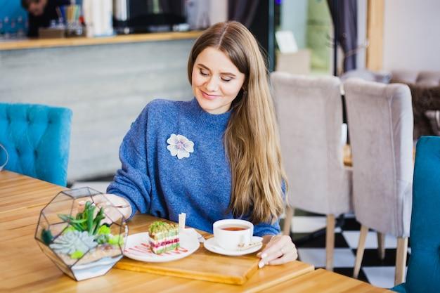 Retrato de uma menina bonita, aparência europeia em um café, belo interior