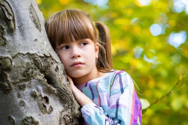 Retrato de uma menina bonita apoiada no tronco de uma árvore no outono parque relaxante