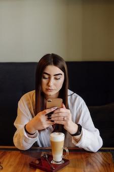 Retrato de uma menina bonita, bebendo chá quente ou café em um café com seu telefone celular.