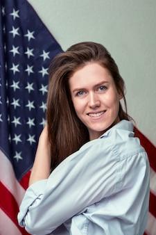 Retrato de uma menina bonita camisa na parede da bandeira americana close-up