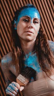 Retrato de uma menina bonita com bodyart facial azul com lantejoulas. a artista desenha arte corporal em si mesma