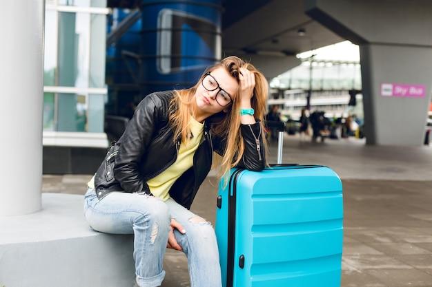 Retrato de uma menina bonita com cabelo comprido em copos, sentado do lado de fora no aeroporto. ela usa um suéter amarelo com jaqueta preta e jeans. ela se inclinou para a mala e está entediada de esperar.