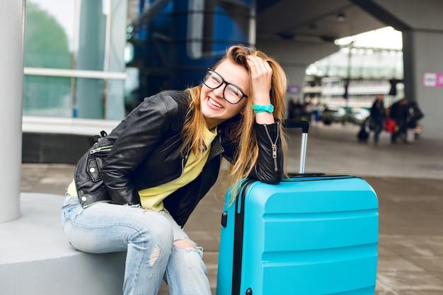 Retrato de uma menina bonita com cabelo comprido em copos, sentado do lado de fora no aeroporto. ela usa um suéter amarelo com jaqueta preta e jeans. ela se inclinou para a mala e sorrindo para a câmera.