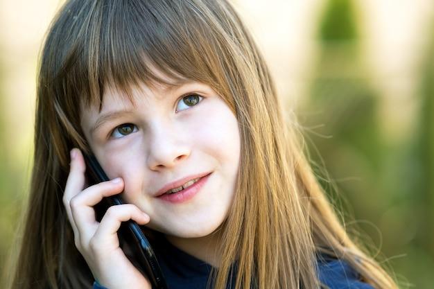 Retrato de uma menina bonita com cabelo comprido, falando no celular.