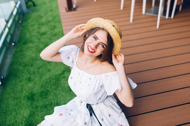 Retrato de uma menina bonita com cabelo comprido no chapéu, sentado no chão de madeira ao ar livre. ela usa um vestido branco com ombros nus, batom vermelho. ela está sorrindo para a câmera. vista de cima.
