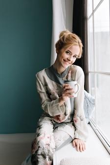 Retrato de uma menina bonita com cabelo loiro preso, sentado no parapeito da janela com uma xícara de café ou chá na mão, tempo de manhã feliz. parede turquesa. vestido com pijama de seda com flores.
