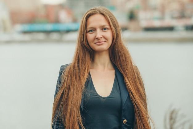 Retrato de uma menina bonita com cabelo vermelho no fundo da paisagem urbana