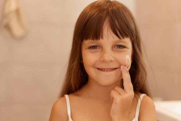 Retrato de uma menina bonita com creme facial na bochecha, apontando o dedo n seu rosto, olhando sorrindo diretamente para a câmera, vestindo camiseta branca sem mangas.