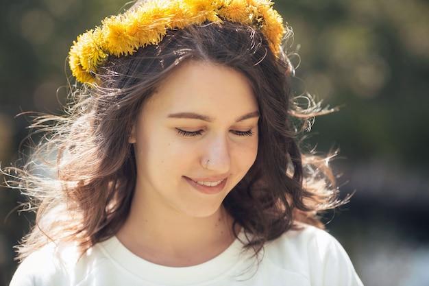 Retrato de uma menina bonita com dentes de leão. garota romântica com uma coroa de flores.