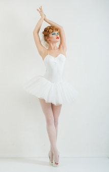 Retrato de uma menina bonita com os lábios de maquiagem moda vermelho, penteado elegante. no vestido de balé.
