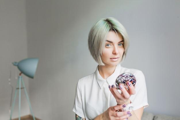 Retrato de uma menina bonita com penteado curto cinza em pé no estúdio cinza. ela usa vestido branco e maquiagem leve. ela está segurando um espelho nas mãos e olhando para a câmera.