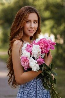 Retrato de uma menina bonita com um buquê de flores do verão. caminhar na cidade. fundo desfocado