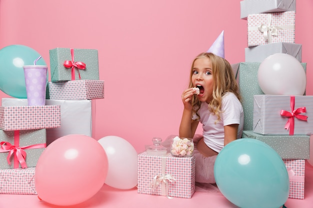 Retrato de uma menina bonita com um chapéu de aniversário comemorando