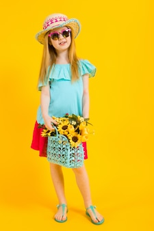 Retrato de uma menina bonita com um chapéu, óculos escuros, vestido de verão e sandálias.