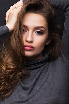 Retrato de uma menina bonita com um suéter cinza sobre um fundo preto