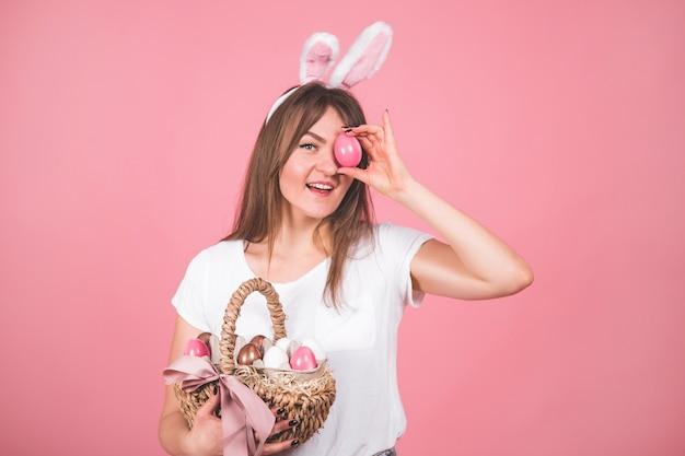 Retrato de uma menina bonita com uma cesta de ovos de páscoa em pé