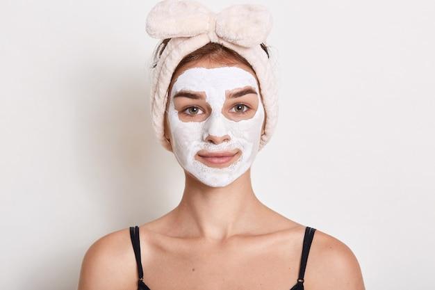 Retrato de uma menina bonita com uma faixa na cabeça, aplicando a máscara facial, olhando diretamente para a câmera com uma expressão facial calma, fazendo procedimentos de limpeza para a pele do rosto.