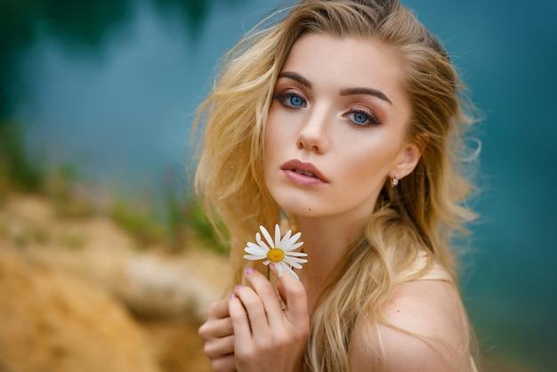 Retrato de uma menina bonita com uma margarida nas mãos, maquiagem bonita