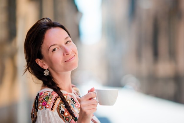Retrato de uma menina bonita com uma xícara de café na rua. turista caucasiana desfrutar de suas férias na europa na cidade vazia