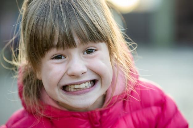 Retrato de uma menina bonita criança ao ar livre em um dia ensolarado ensolarado de outono.